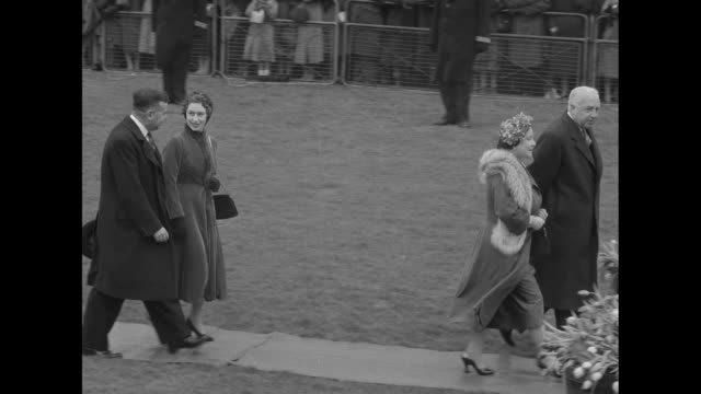 Queen Elizabeth II Queen Mother Elizabeth and Princess Margaret walk on path on airfield with men / rear shot the royal women move toward a BOAC...