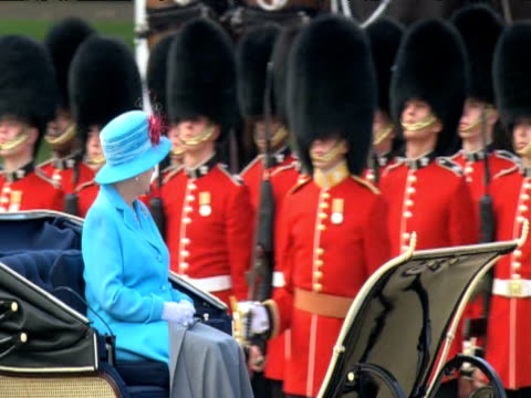 stockvideo's en b-roll-footage met queen elizabeth ii rides past line of footguards in horse drawn carriage during trooping the colour parade london 13 june 2009 - designerkleding