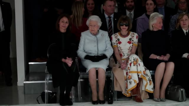 Queen Elizabeth II sits next to Anna Wintour as they view Richard Quinn's runway show before presenting him with the inaugural Queen Elizabeth II...