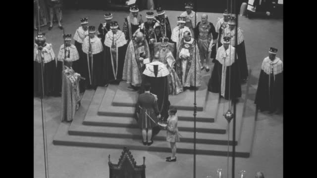 queen elizabeth ii sits on the homage throne on raised platform surrounded by bishops, and high officials in ermine trimmed robes, her husband prince... - archbishop of canterbury stock videos & royalty-free footage