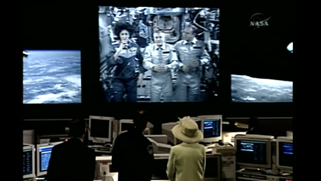 maryland greenbelt goddard space flight center back view of queen as stands with foale to watch giant screen showing video linkup with astronauts - television show stock videos & royalty-free footage