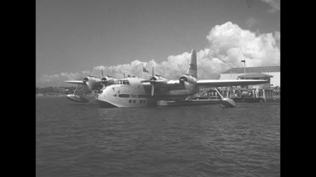 queen elizabeth ii walks across dock catwalk and boards tasman empire airways seaplane, she is followed by military officer and philip, duke of... - 水上飛行機点の映像素材/bロール