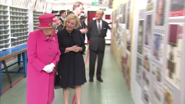 queen elizabeth ii, wearing bright pink, visited a royal mail delivery office in windsor, where she had a look at a variety of royal commemorative... - briefmarke stock-videos und b-roll-filmmaterial