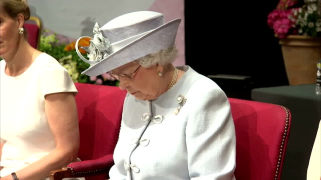 queen elizabeth ii wearing powder blue coat and hat sitting on stage listening to speech along with anne, princess royal and sophie countess of... - royal blue stock videos & royalty-free footage