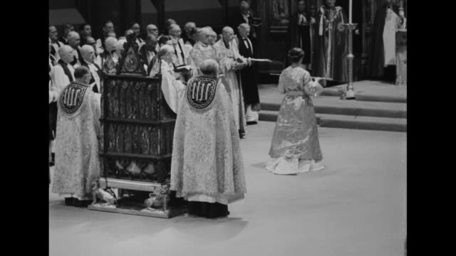 queen elizabeth ii wearing shiny robe rises from king edward's chair carrying sword of state and walks to altar passing it to clergyman who places it... - coronation of queen elizabeth ii stock videos and b-roll footage