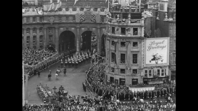 Queen Elizabeth II's coronation coach rounds the corner and approaches decorated Admiralty Arch sailors line both sides of street behind them crowds...