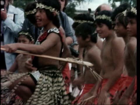 vídeos y material grabado en eventos de stock de queen elizabeth ii's silver jubilee tour ms maori boys doing warrior act ms ditto ms queen along with flowers ms boy warrior performs with spear zoom... - 1977