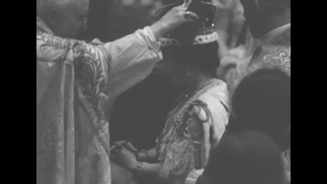 vídeos y material grabado en eventos de stock de queen elizabeth kneels during coronation ceremony / montage archbishop of canterbury crowns queen / queen walks with her sceptre with cross and ivory... - corona accesorio de cabeza