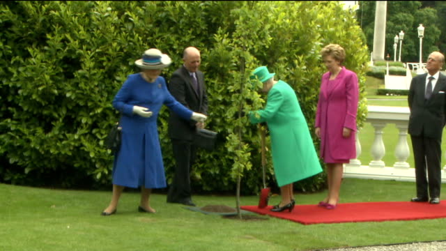 Queen Elizabeth plants tree at Aras an Uachtarain Queen Elizabeth using spade to perform treeplanting ceremony as fanfare played