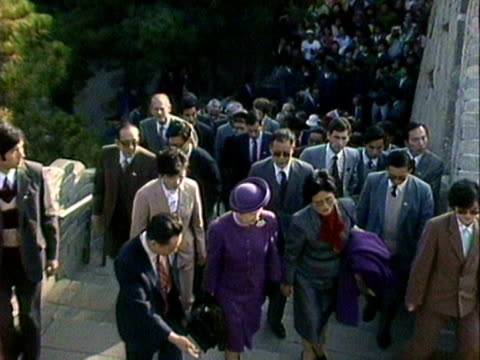 Queen Elizabeth Prince Philip and their entourage walk up steps to the Great Wall of China October 1986