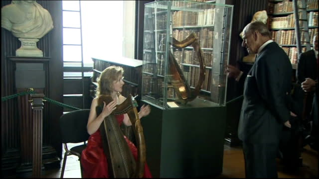 queen elizabeth visit queen visits trinity college library philip watching as harpist plays next to display case housing oldest harp in ireland sot /... - harp stock videos & royalty-free footage
