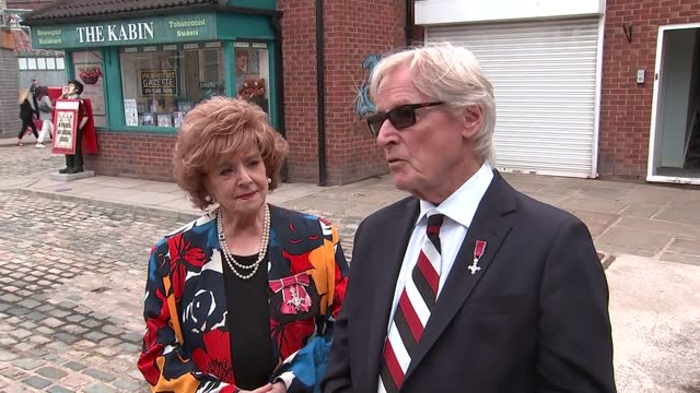 """queen elizabeth visits coronation street set; england: manchester: coronation street set: ext barbara knox and william roache interview sot. - """"the... - soap opera stock videos & royalty-free footage"""