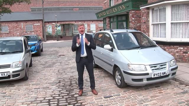 queen elizabeth visits coronation street set to mark 60 years of tv sop opera; england: manchester: itv studios: coronation street set: ext reporter... - soap opera stock videos & royalty-free footage
