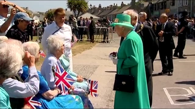 queen elizabeth visits scilly isles; various of queen elizabeth walkabout meeting group of elderly people seated in wheelchairs and waving union jack... - isles of scilly stock videos & royalty-free footage