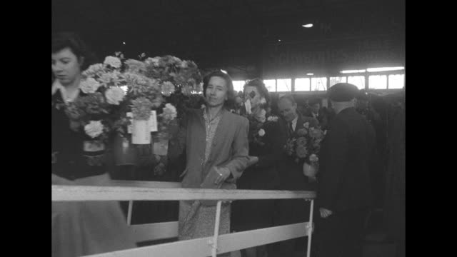 rms queen elizabeth / vyacheslav molotov / large bouquets of flowers being carried on gangplank / sen tom connally / the looming ship and wellwishers... - イングランド サウサンプトン点の映像素材/bロール