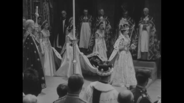 queen elizabeth wearing crown and holding scepter and rod with maids of honor holding her train walks past guests at coronation ceremony - coronation stock videos and b-roll footage