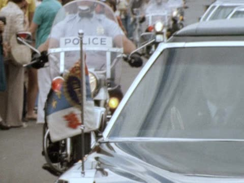 queen elizabeth's motorcade and police escort drive to the olympic village in montreal for the 1976 olympic games. crowds line the streets and one... - montreal video stock e b–roll