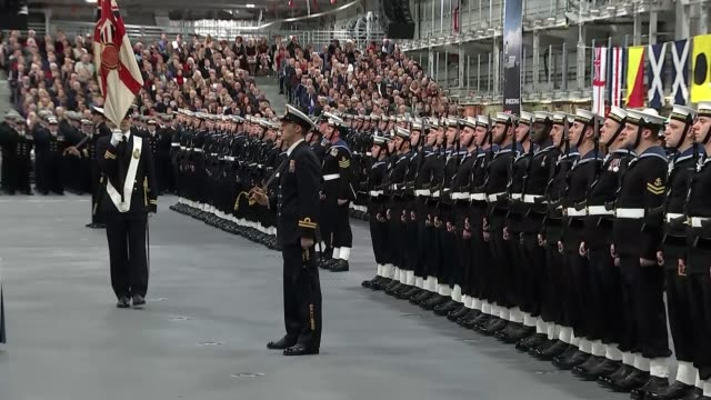 vidéos et rushes de queen formally commissions hms queen elizabeth aircraft carrier flag carried along in front of ranks of royal navy sailors lined up for commissioning... - royal navy