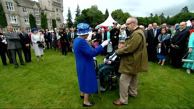 queen garden party at balmoral; gvs queen meeting guests on lawn / gvs queen meeting raf officer / gvs queen meeting man in wheelchair / gvs queen... - former stock videos & royalty-free footage