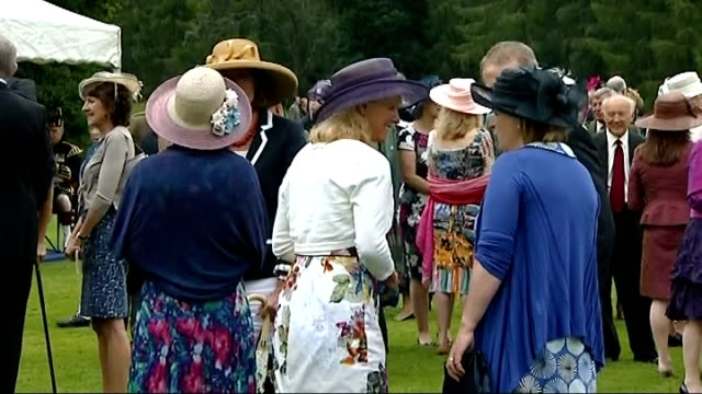 queen garden party at balmoral; scotland: balmoral castle: ext gvs people outside balmoral castle / various shots of guests on lawn chatting /... - royal blue stock videos & royalty-free footage