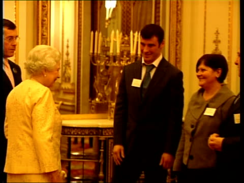 Queen hosts Achievers Reception at Buckingham palace Queen Elizabeth II into room shakes hands with Calzaghe and unidentified woman Queen shaking...