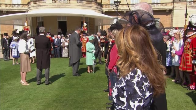 Queen hosts Buckingham Palace Garden Party ENGLAND London Buckingham Palace EXT GVs Guests mingling / Queen emerges and walks down the stairs to join...