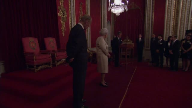 queen hosts engineers reception at buckingham palace queen and prince philip into throne room and past guests / queen and duke of edinburgh on stage... - throne stock videos & royalty-free footage