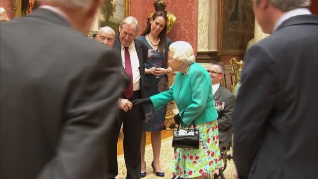 Queen hosts VC and GC Association reception ENGLAND London Buckingham Palace Queen Elizabeth II and Peter Norton entering reception and greeting...