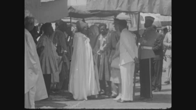 tamale durbar ext queen elizabeth and officials walking under large umbrella various of queen speaking to dignitaries close view of queen and duke... - ghana stock videos & royalty-free footage