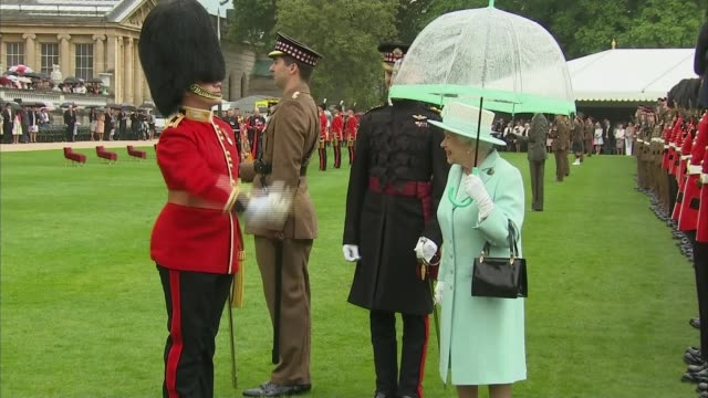 queen inspects scots guard at buckingham palace; england: london: buckingham palace: ext / rain queen elizabeth ii watching scots guard / queen... - examining stock-videos und b-roll-filmmaterial