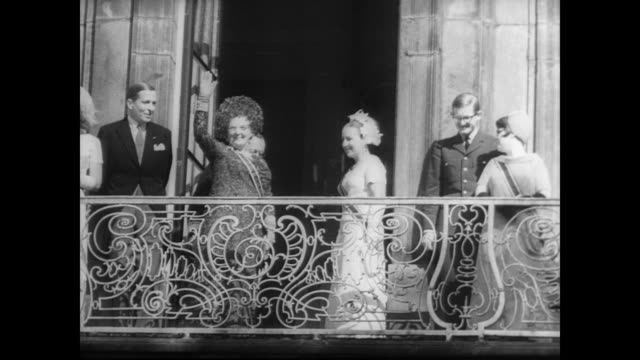 queen juliana arrives at the dutch parliament in a golden carriage accompanied by regal footmen in front of public crowd for the official opening of... - フットマン点の映像素材/bロール