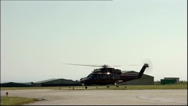 queen makes first visit to scilly isles since 1967; helicopter carrying the queen and prince philip landing - イングランド南西部点の映像素材/bロール