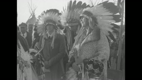 queen marie and princess ileana, prince nicholas, three blackfoot indians in headdresses and crowd of people walk toward camera, snow capped mountain... - headdress stock videos & royalty-free footage