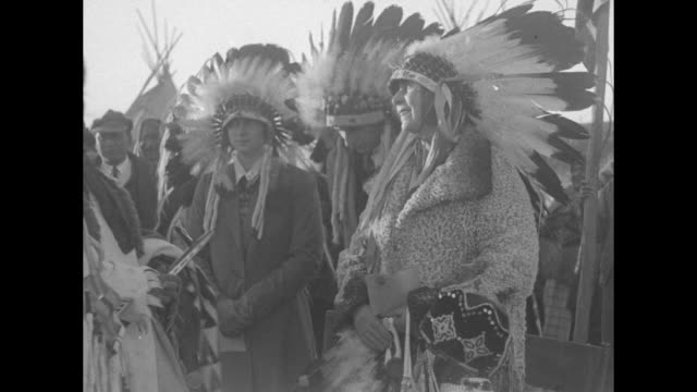 queen marie and princess ileana prince nicholas three blackfoot indians in headdresses and crowd of people walk toward camera snow capped mountain... - ネイティブアメリカン点の映像素材/bロール
