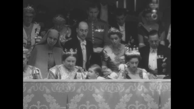 queen mary and princess margaret with lowered heads prince charles fidgeting / pan left to other ladies in box / six maids of honor / box with queen... - princess margaret 1950 stock videos and b-roll footage