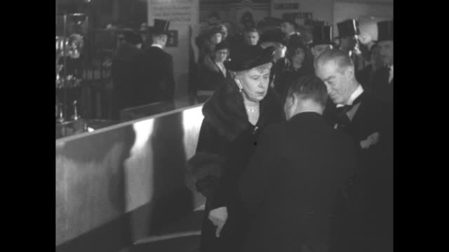 vs queen mary escorted to event at opening of british trade fair she speaks with participant walks past display cases containing silver / note exact... - participant stock videos & royalty-free footage