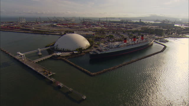 stockvideo's en b-roll-footage met aerial queen mary, spruce goose and port at long beach harbor, long beach, california, usa - long beach californië