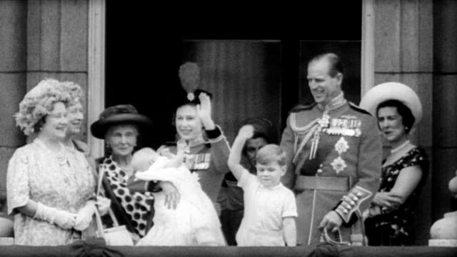 vídeos de stock e filmes b-roll de / queen mother and other members of the royal family watch the queen's birthday parade from the balcony of buckingham palace / aerial view of passing... - 1964