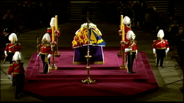 coffin lying in state; england: int queen mother's coffin sitting on catafalque with guardsmen standing vigil as mourners file past, guardsmen down... - 正装安置点の映像素材/bロール