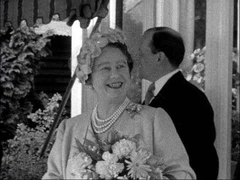 Queen Mother visits Ockenden Venture ENGLAND Surrey Woking Ockenden Venture EXT Queen Elizabeth the Queen Mother accepts bouquet from small girl CU...