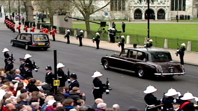 Queen mother's funeral cortege along Royal cars along towards / Hearse pulls away from Westminster Abbey as followed by other cars / Coffin in hearse...