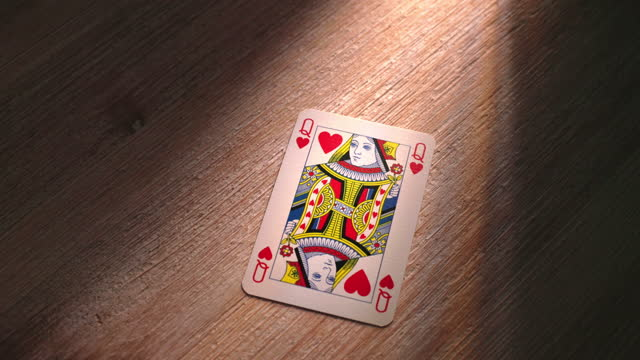 queen of hearts playing card dropping onto a wooden table. sm. - royalty stock videos & royalty-free footage