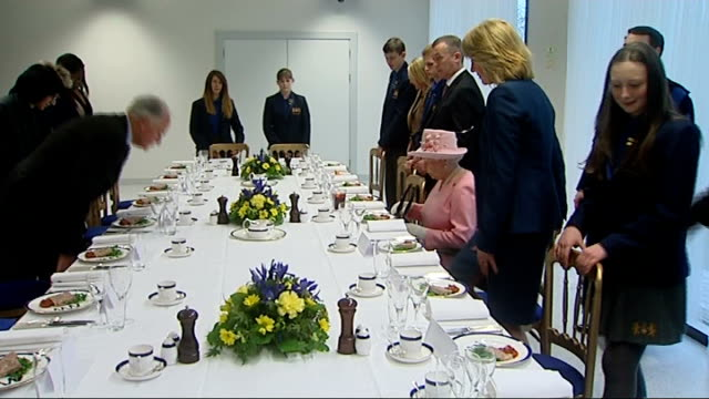 queen opens drapers academy school in essex; queen into dining area / prayers said and all sit / queen meets more staff, including kitchen staff /... - フラワーアレンジメント点の映像素材/bロール