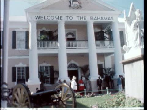 queen opens parliament; bahamas: nassau: ext queen elizabeth ii along in open-top car waving gvs bahamian parliament building gvs military band gvs... - bahamas stock-videos und b-roll-filmmaterial