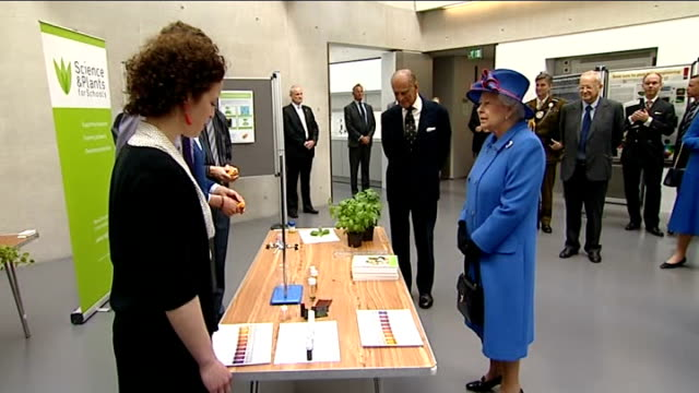 Queen opens Sainsbury Laboratory at University of Cambridge Botanic Garden Woman speaking with Queen / Student speaking to Philip as showing him pot...