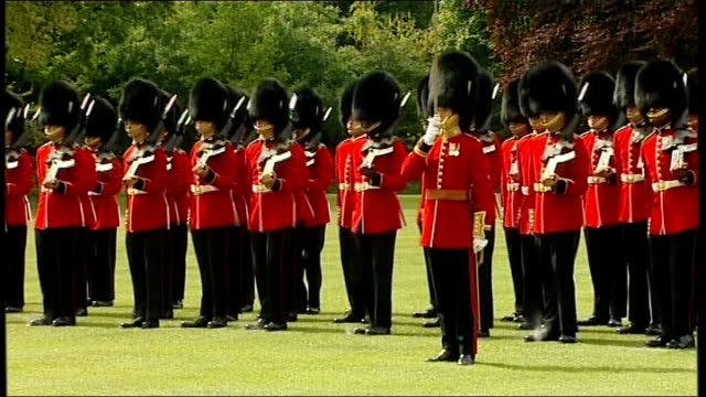 queen presenting regimental colours to grenadier guards guards present arms / national anthem played sot / guards remove headdress and give three... - headdress stock videos & royalty-free footage