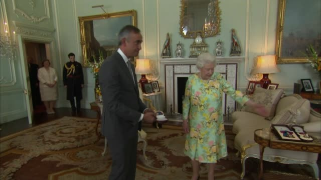 queen presents insignia of members of the order of merit england london buckingham palace photography*** ara darzi along and recieving order of merit... - insignia stock videos and b-roll footage