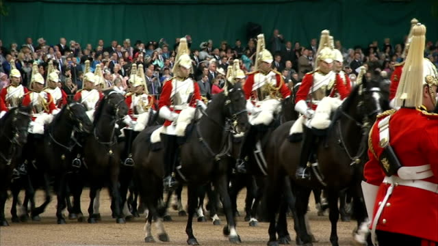 Queen presents new standards to Household Cavalry Various shots of mounted soldiers in Household Cavalry along in parade past Queen / tanks along in...