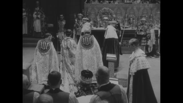 queen steps up to kneeler and kneels pan back to prince philip standing at kneeler / queen stands and turns walks back turns again / she stands at... - coronation of queen elizabeth ii stock videos and b-roll footage