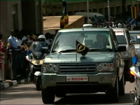 queen visit to aids clinic in kampala; car carrying queen and prince philip along with police escort - kampala stock-videos und b-roll-filmmaterial